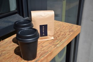 a bag of coffee beans and two cups of takeaway coffee
